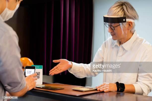 感染の拡大を抑制するために、顔の警備員とスマートフォンの支払いを奨励します。 - フェイスシールド ストックフォトと画像
