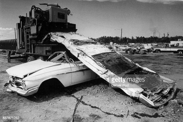 End of the Line For Unwanted Car An abandoned and unclaimed car is picked up top by a fork truck and deposited center in a mobile crusher owned by...
