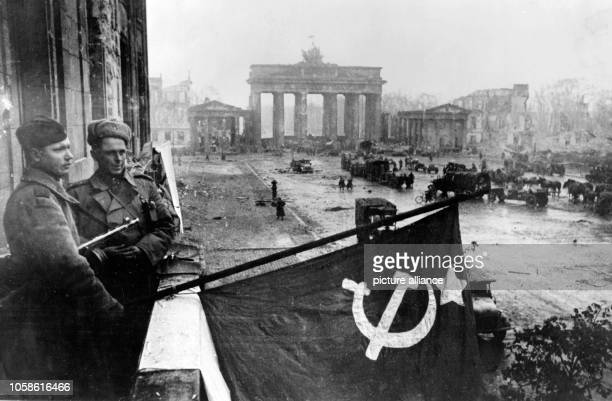 End of the war in Berlin 1945 - Red Army soldiers hoist the Soviet flag from a balcony of the renowned Hotel Adlon in front of Soviet units gathering...