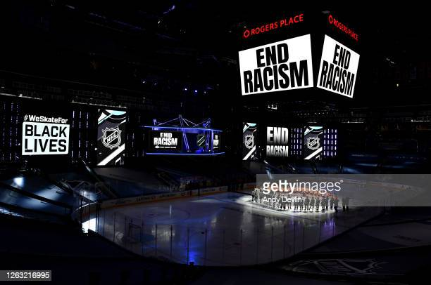 End Racism signs are seen as Mathew Dumba of the Minnesota Wild speaks at center ice before Game One of the Western Conference Qualification Round...
