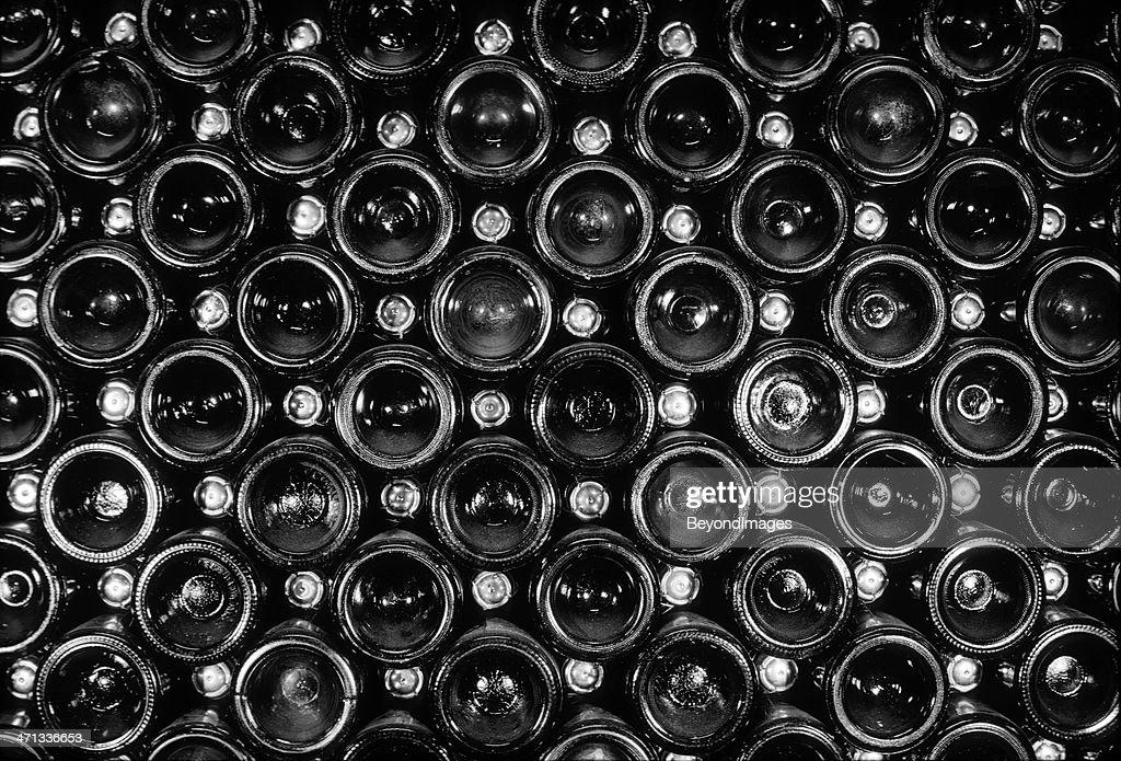 end view of vintage sparkling wine bottle stack stock