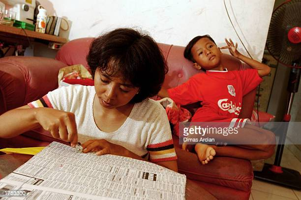 Endang Isnani learns how to sew while her oldest son Garil Arnanda sits behind her in the living room of their home January 30 2003 in Denpasar Bali...