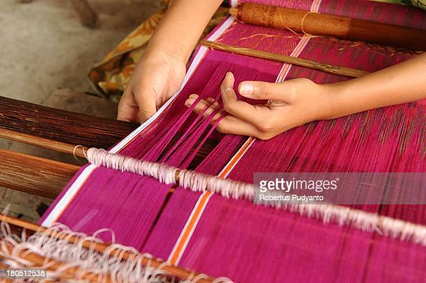 Endang the youngest known traditional ulos weaver makes an ulos on a loom on September 14 2013 in Samosir North Sumatra Indonesia Endang Ernawati...
