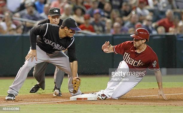Ender Inciarte of the Arizona Diamondbacks advances to third base safely on a wild pitch as Nolan Arenado of the Colorado Rockies can't handle the...