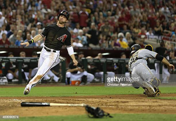 Ender Inciarte of the Arizona Diamondbacks slides in to score a run past catcher Russell Martin of the Pittsburgh Pirates during the fifth inning of...