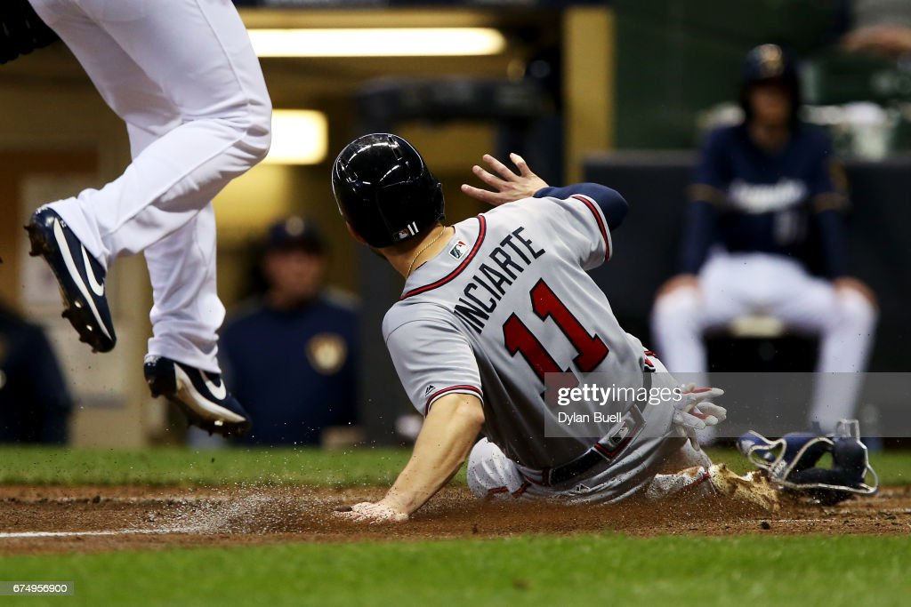Ender Inciarte #11 of the Atlanta Braves slides into home plate past Jimmy Nelson #52 of the Milwaukee Brewers to score a run on a passed ball in the fifth inning at Miller Park on April 29, 2017 in Milwaukee, Wisconsin.