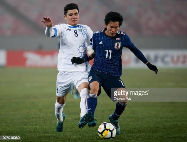 Endo Keita of Japan and Yakhshiboev Jasurbek of Uzbekistan in action during AFC U23 Championship Quarterfinal between Japan and Uzbekistan at...