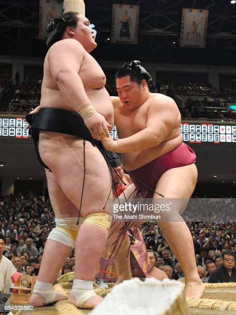 Endo pushes Mongolian ozeki Terunofuji out of the ring to win during day one of the Grand Sumo Summer Tournament at Ryogoku Kokugikan on May 14 2017...