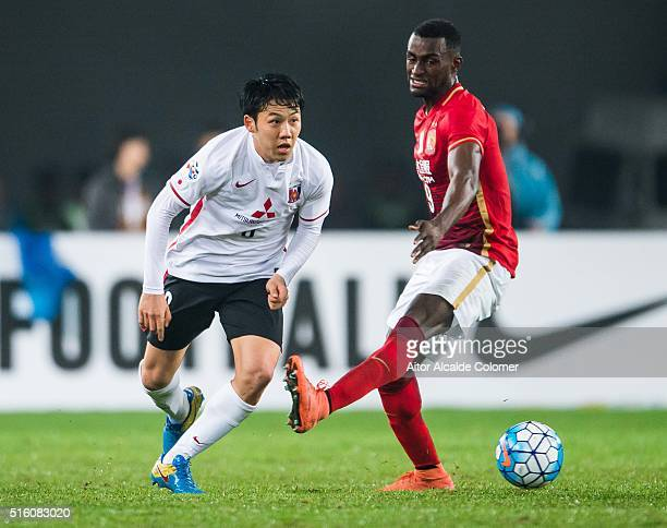 Endo Wataru of Urawa Red Diamonds being followed by Jackson Martinez of Guangzhou Evergrande during the AFC Champions League match between Guangzhou...