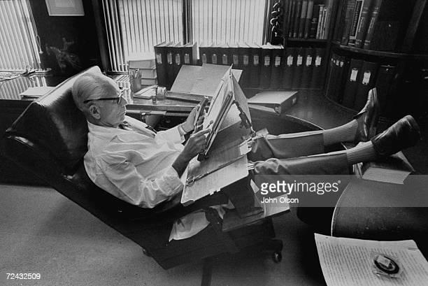 Endocrinologist Dr Hans Selye with feet up on desk dictating into microphone at lap worktable of his own design in his office at University of...