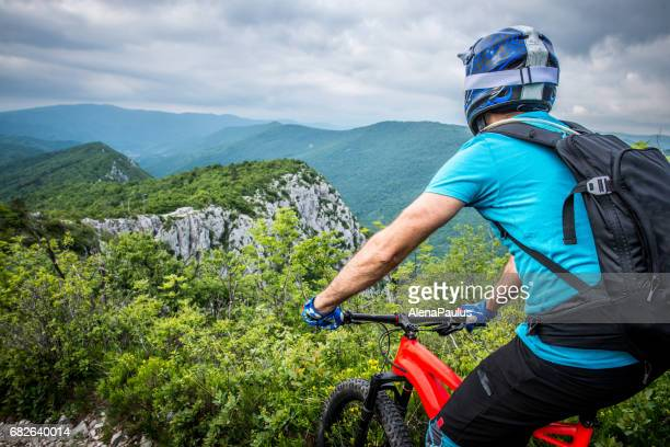 Enduro All Mountain E bike rider - adrenaline MTB trail - looking at view