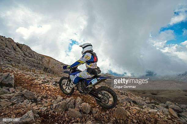 Enduro rider climbing up to the mountain peak