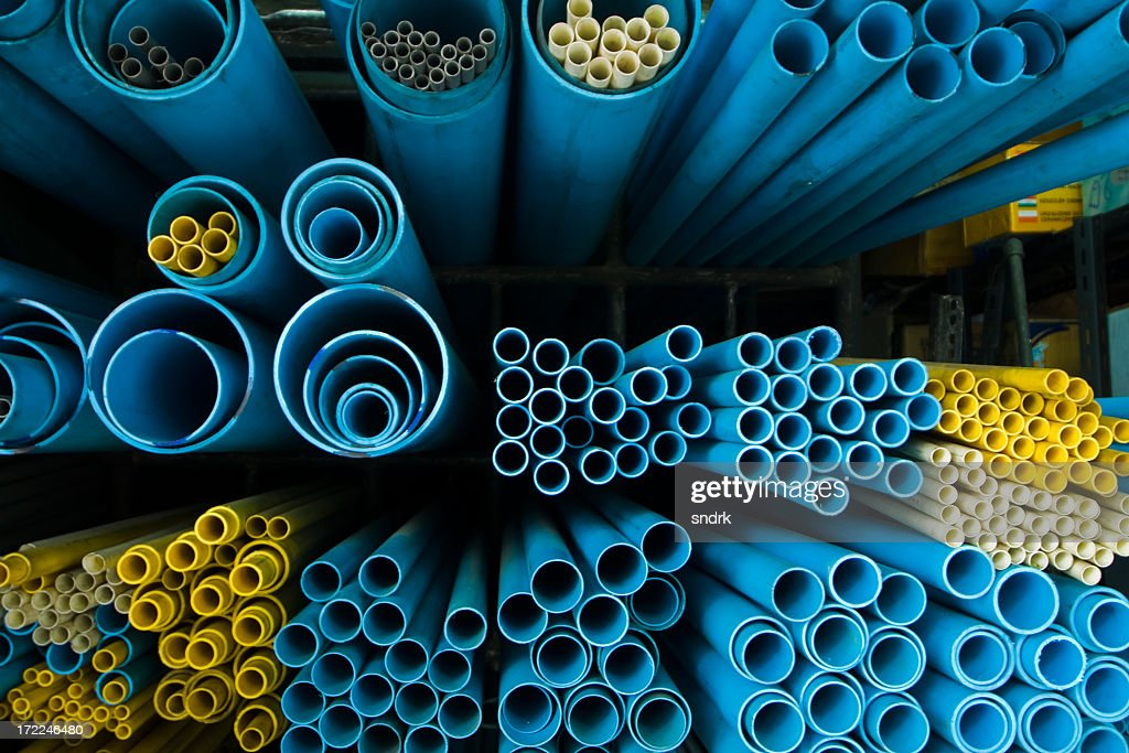 End-view of groups of different sized blue and yellow tubes : Stock Photo