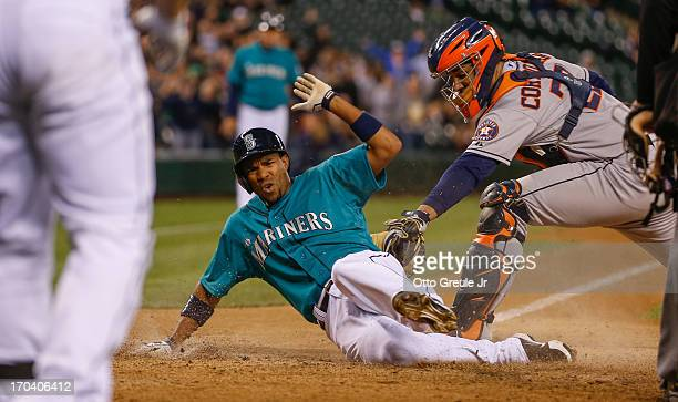 Endy Chavez of the Seattle Mariners scores on an RBI single by Nick Franklin against catcher Carlos Corporan of the Houston Astros in the eighth...