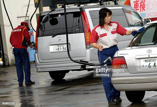 Eneos employees fill customers' tanks at a service station in Tokyo Thursday June 30 2005