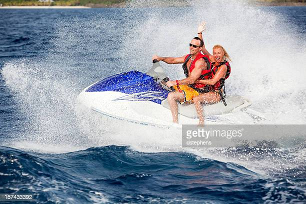 Energetic adult couple riding wave runner