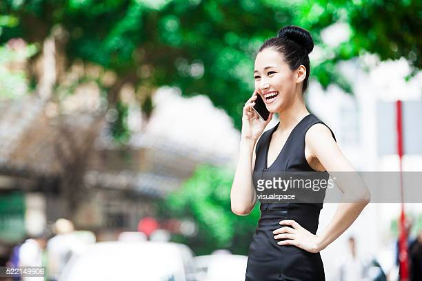 Energetic Asian Woman Talking On The Phone In The Street