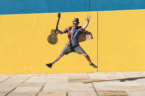 Energetic funny guy jumping with an electric guitar in front of a blue an yellow wall