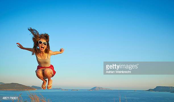 Energetic girl jumping mid air, Kas, Turkey