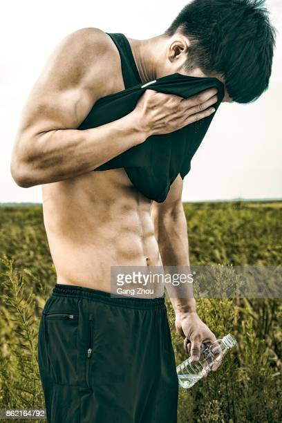 energetic man wiping sweat with holding bottle of water - asian six pack stock photos and pictures