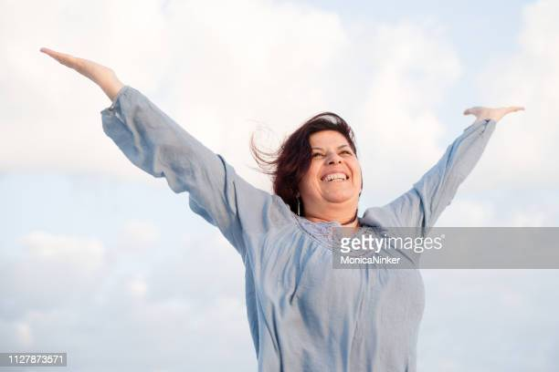 energetic mature woman enjoying life - fat woman at beach stock photos and pictures