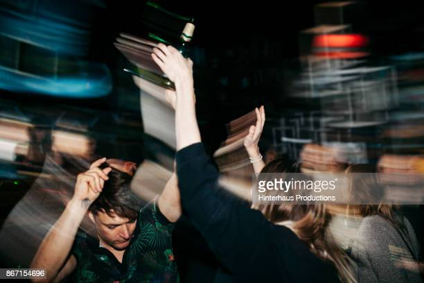 energetic scene of people on dancefloor at nightclub - party stock-fotos und bilder