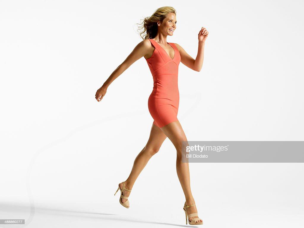 Energetic woman jumping in studio : Stock Photo
