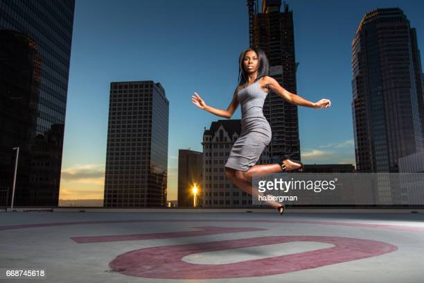 energetic woman jumping on rooftop helipad - helipad stock photos and pictures