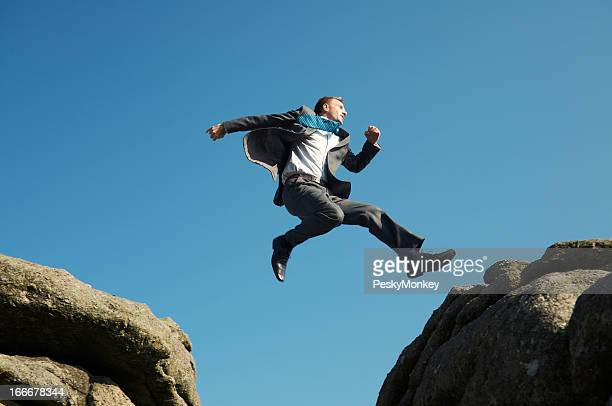 Energetic Young Man Businessman Jumping into Blue Sky between Rocks