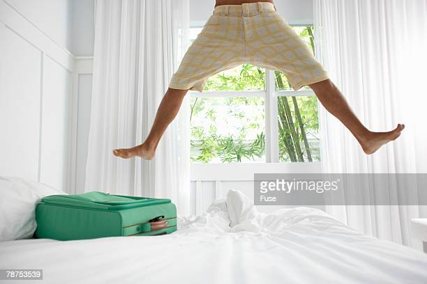 Energized Young Man Jumping on Hotel Bed