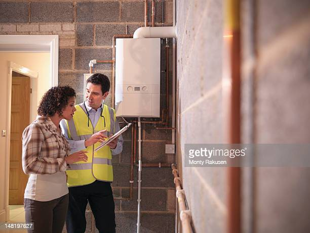 energy advisor discussing usage of energy efficient boiler with woman in home - energy efficient stock pictures, royalty-free photos & images