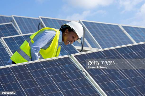 energy engineer woman working on a roof with solar panels. - solar powered station stock pictures, royalty-free photos & images