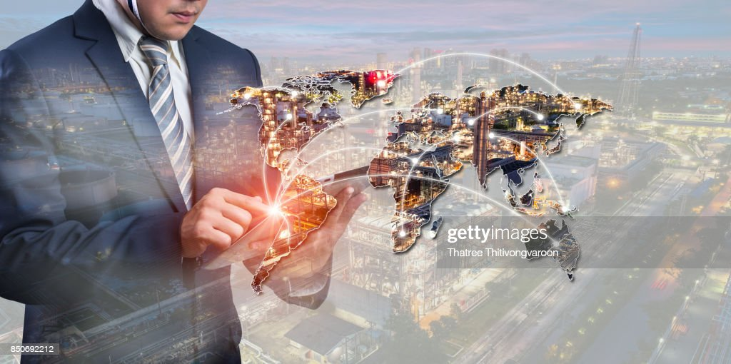 energy power concept : double exposure of businessmen using smart phone with Oil and gas industry - refinery factory - petrochemical plan on world map background : Stock Photo