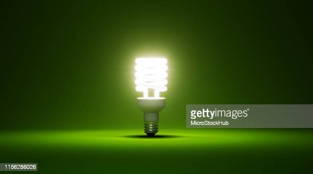 energy saver light bulb glowing on green background - energy efficient lightbulb stock pictures, royalty-free photos & images