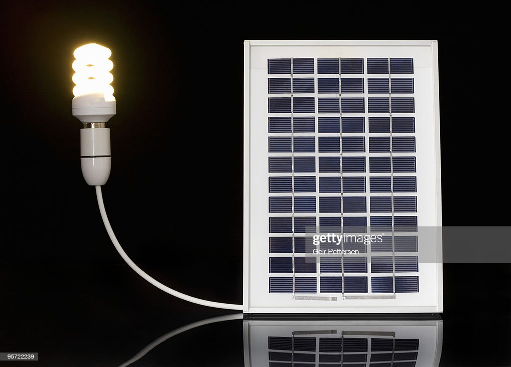 Energy Saving Light Bulb Connected To Solar Panel Stock