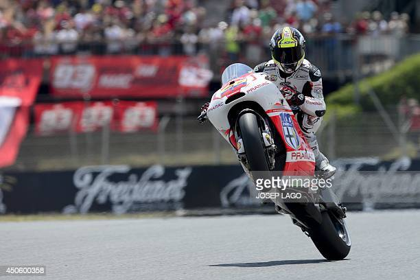 Energy TI Pramac Racing's Colombian rider Yonny Hernandez pulls a wheelie after the Moto GP qualifying session of the Catalunya Grand Prix at the...