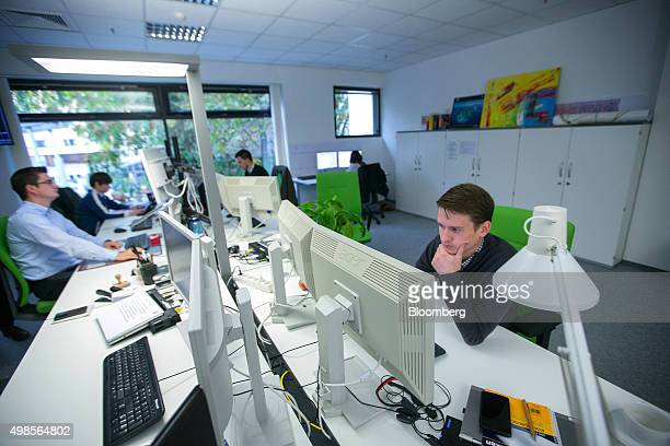 Energy traders monitor data on desktop computer screens in the offices of electric utility company Grundgruen Energie GmbH in Berlin Germany on...