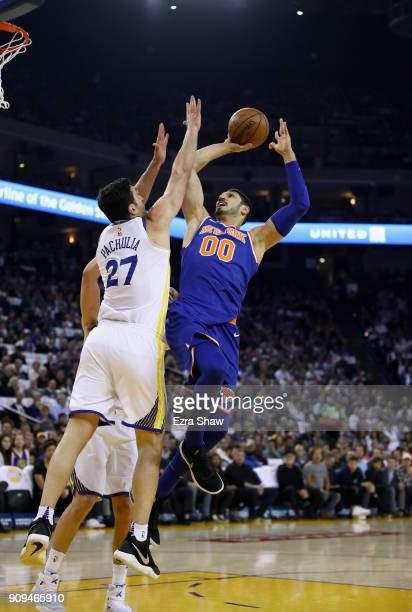 Enes Kanter of the New York Knicks shoots over Zaza Pachulia of the Golden State Warriors at ORACLE Arena on January 23 2018 in Oakland California...