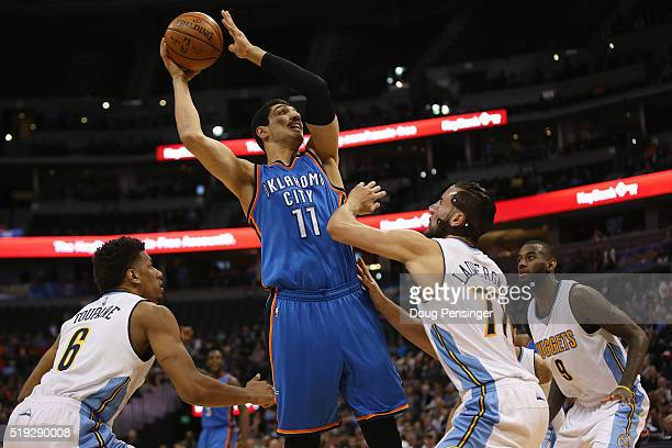 Enes Kanter of the Oklahoma City Thunder takes a shot against Axel Toupane and Joffrey Lauvergne of the Denver Nuggets at Pepsi Center on April 5...