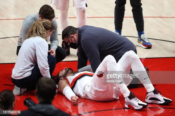 Enes Kanter of the Portland Trail Blazers is attended to after being injured in the third quarter against the Miami Heat at Moda Center on April 11,...