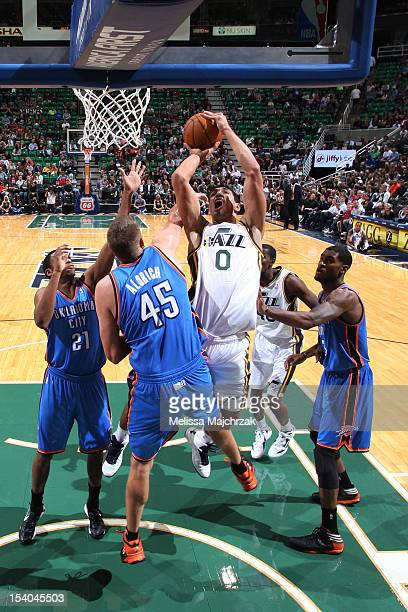 Enes Kanter of the Utah Jazz goes to the basket against Cole Aldrich of the Oklahoma City Thunder at Energy Solutions Arena on October 12 2012 in...