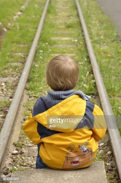 enfant assis face aux rails - assis ストックフォトと画像