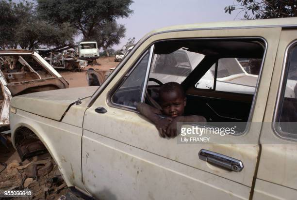 Enfant chargé de la récupération des pièces dans une casse de voitures à Niamey en décembre 1986 Niger