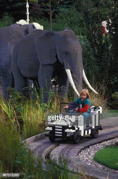 Enfant dans une voiture passant à côté de faux éléphants au parc Legoland le 28 août 1988 à Billund Danemark