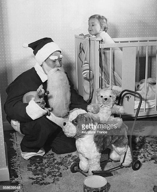 Enfant debout dans son lit espionnant le Pere Noel qui depose des jouets dans sa chambre