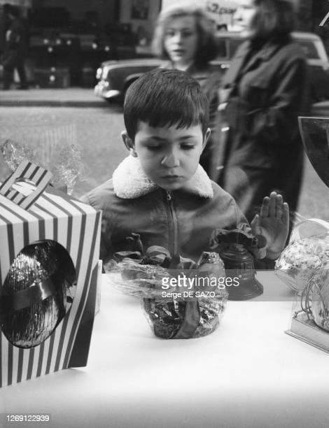 Enfant devant la vitrine d'une chocolaterie à Paris, circa 1970, France.