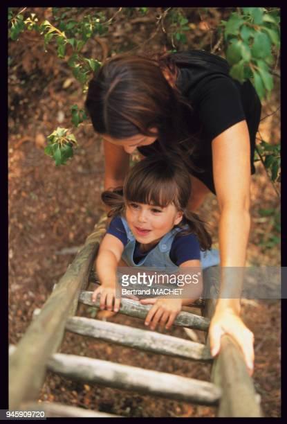 Enfant grimpant sur une ?chelle.