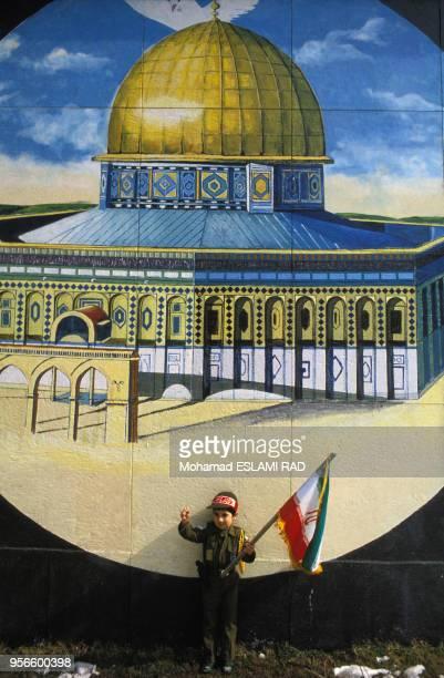 Enfant habillé en Pasdaran devant une peinture murale représentant la Mosquée alAqsa de Jérusalem en 1985 à Téhéran Iran