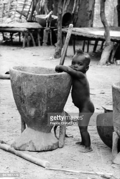 Enfant jouant avec un pilon à mil au Niger en 1978
