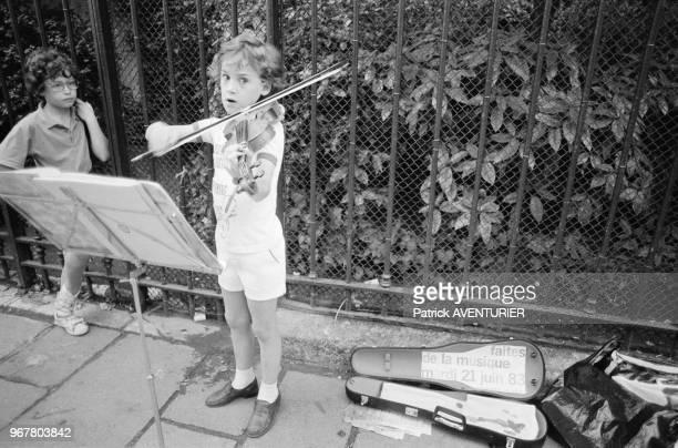 Enfant jouant du violon dans la rue lors de la Fête de la Musique à Paris le 21 juin 1983 France